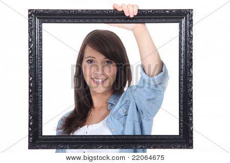 teenage girl behind a painting frame