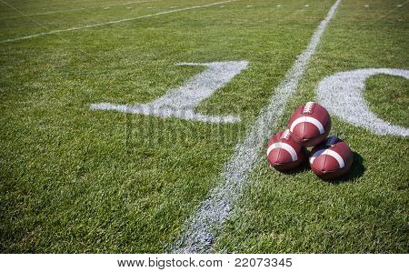 footballs positioned together on the sideline of a football field