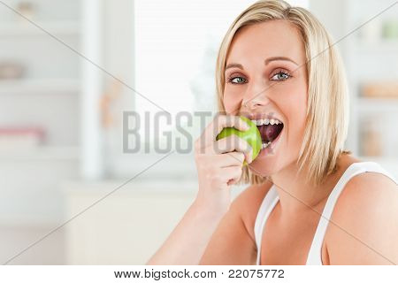 Young Blonde Woman Sitting At Table Eating A Green Apple While Looking Into The Camera