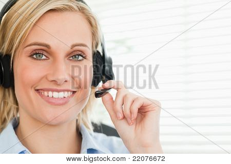 Close Up Of A Smiling Businesswoman With Headset Looking Into Camera