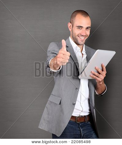 Cool businessman using touch pad on grey background