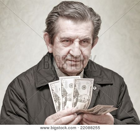 elderly happy man with pack of money