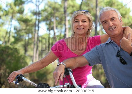Older couple riding bikes in the countryside