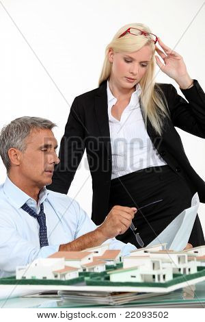 a boss and his female assistant thinking behind a subdivision model