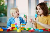 Little Boy Playing With Construction Blocks While His Mother Working On Computer poster