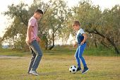 Father and his son playing soccer in countryside poster