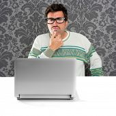 Nerd pensive man with glasses and silly expression in front a laptop computer looking for solution