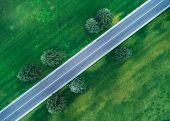 Aerial View Of Road Through Beautiful Green Field poster