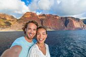 Happy couple tourists on sunset cruise in Na Pali Coast Kauai, Hawaii taking selfie photo with mobil poster