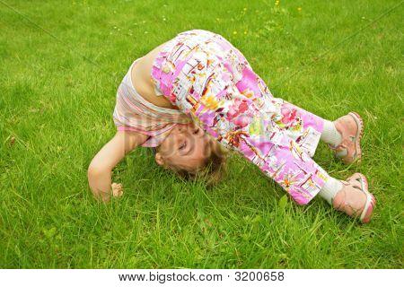 Little Girl Makes Exercise On Grass
