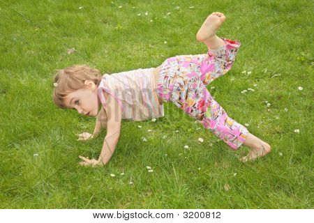 Little Girl Makes Gym Exercise On Grass