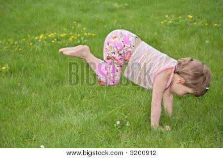 Little Girl Makes Gymnastic Exercise On Grass