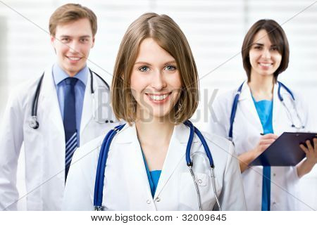 Beautyful young female doctor standing in front of his team and smiling