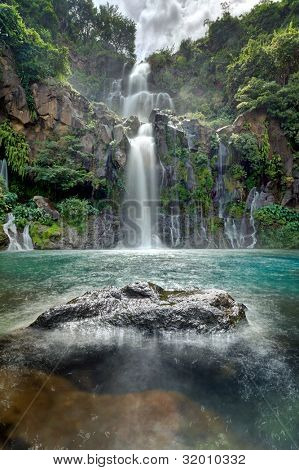 Moving water at the beautiful Trois Bassins waterfall as it plunges into a blue lagoon on Reunion Island.