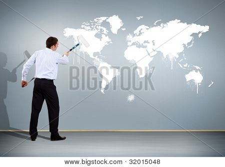 Businessman with paint brush and world map on the background