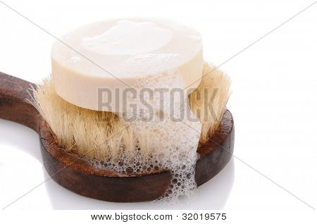 A bar of soap with lather on a bath brush with a wooden handle. Horizontal format over a white background with reflection.