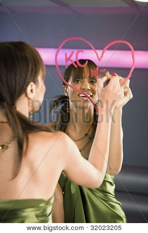 African woman drawing lipstick heart on mirror