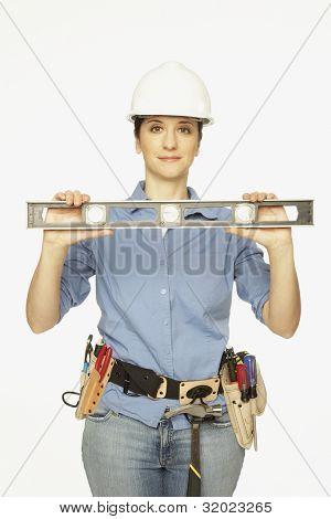 Hispanic female construction worker holding level