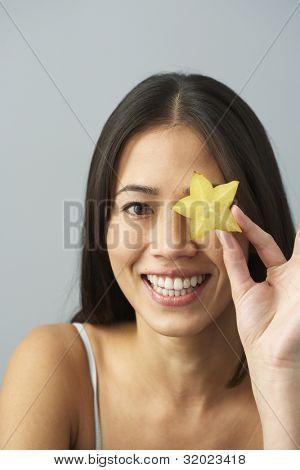 Asian woman holding star fruit over eye