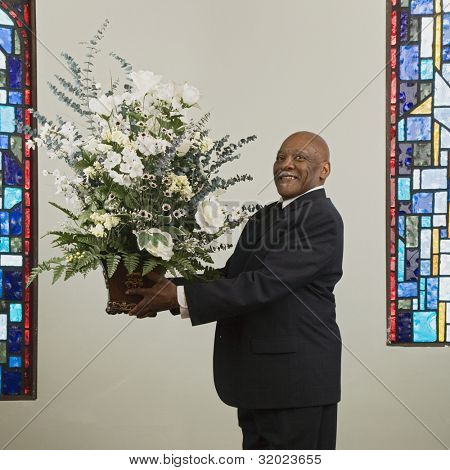 African man holding flower bouquet in church