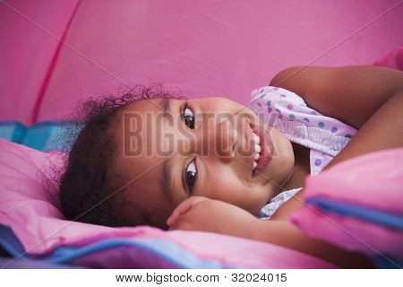 Portrait of African girl laying on sleeping bag