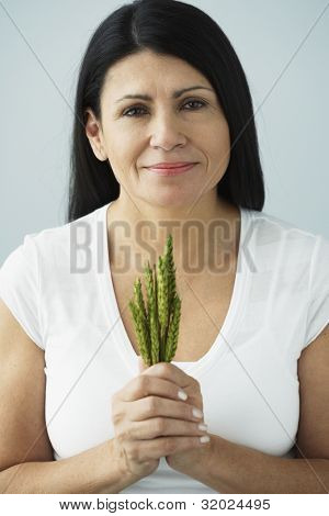 Hispanic woman holding bunch of grain