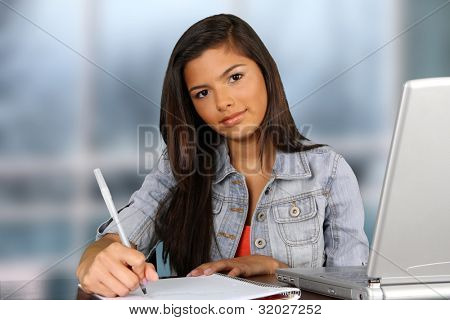 Girl writing at her desk at school