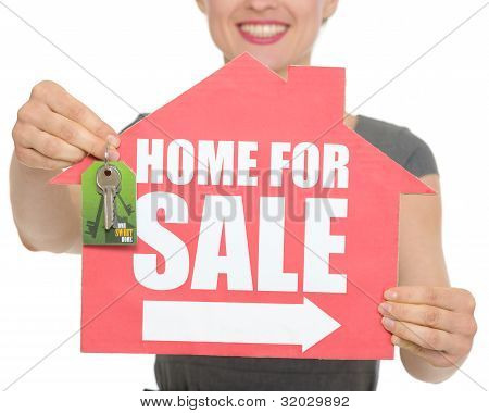 Closeup On Home For Sale Sign And Keys Holding By Happy Female Isolated