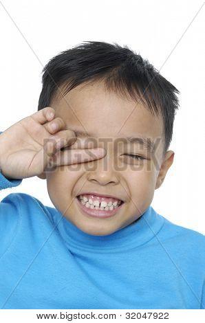 A tired little boy rubbing eyes,