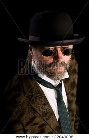 Stilish man in vintage sunglasses pince nez and bowler hat