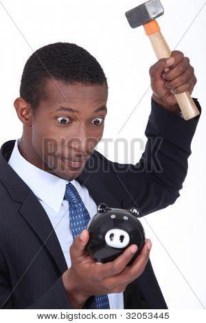Insane man smashing open a piggy bank with a hammer
