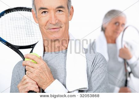 Elderly couple playing tennis together