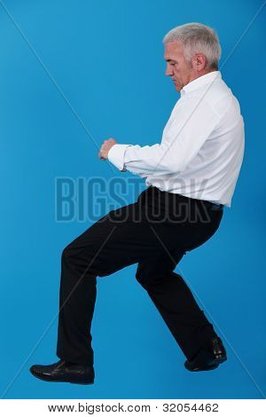 Senior man pulling invisible object
