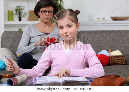 Senior woman knitting and little girl doing homework