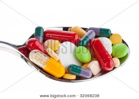many different colored tablets on a spoon. abuse of drugs. isolated on white background.