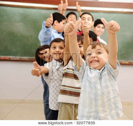 Children at school classroom with thumbs up