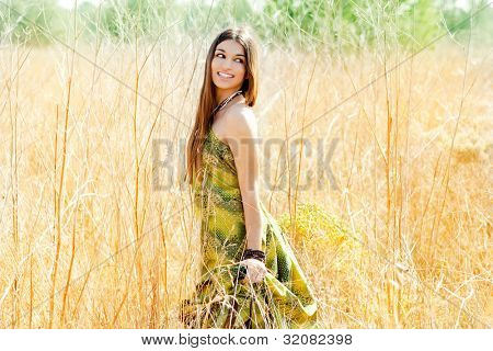Asian indian woman walking outdoors in golden field with green long dress