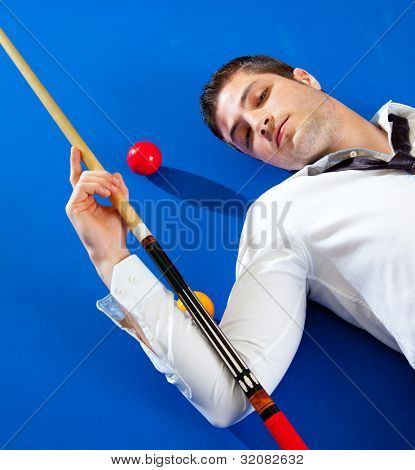 billiard young man player lying on pool blue table with balls