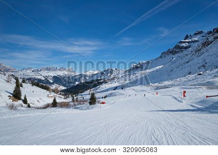 poster of View of a ski resort piste with people skiing in Dolomites in Italy. Canazei, Italy