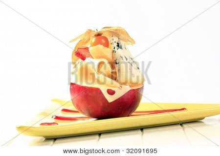 Hard cheese and strawberry on a halved apple decorated with sallow thorn