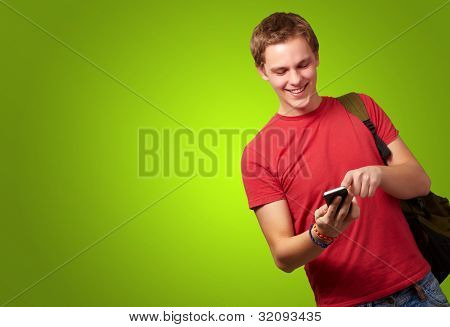 portrait of a young man touching his mobile screen over a green background