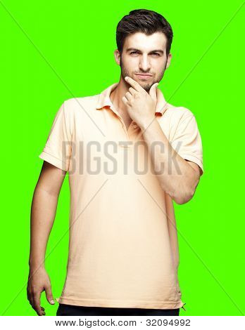 portrait of a young man thinking against a removable chroma key background