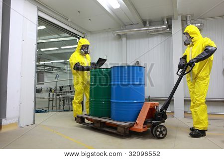 Two specialists in protective uniforms,masks,gloves and boots, dealing with barrels of toxic waste on forklift in factory