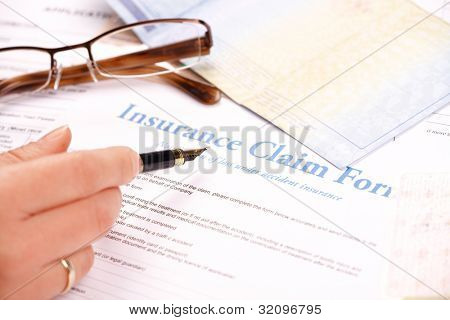 Hand filling in insurance claim form. Other papers like ID or vehicle documents and glases in the background