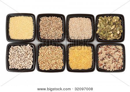 Cereal and grain selection of bulgur wheat, buckwheat, couscous, sesame, pumpkin and sunflower seed, rye grain and wild rice in black square dishes over white background.