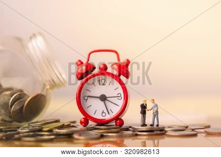 poster of Business Mans And Red Alarm Clock On Stack Of Coins In Concept Of Savings And Money Growing Or Energ