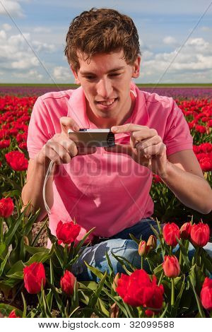 Young man is taking pictures in field with tulips in Holland