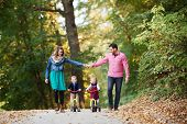 Beautiful Young Family With Small Twins On A Walk In Autumn Forest. poster