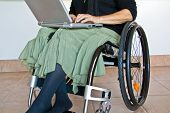 stock photo of disabled person  - Disabled woman sitting in wheelchair working on a laptop - JPG