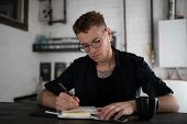 Captivated Man In Eyeglasses Writing In Notebook At Table poster